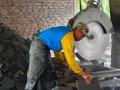 Seorang Pengrajin Sedang Memotong Batu Alam Merapi