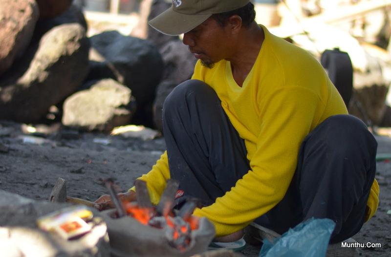 Seorang Pengrajin sedang mipeh / menajamkan kembali Peralatan Pahatnya