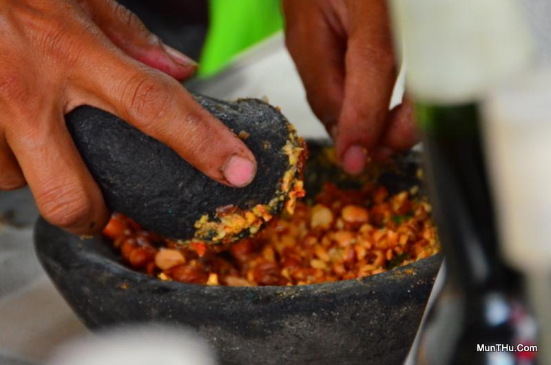 Seorang Penjual Kupat Tahu Magelang Sedang Menghaluskan Bumbu Sambal dengan Cobek dan Munthu